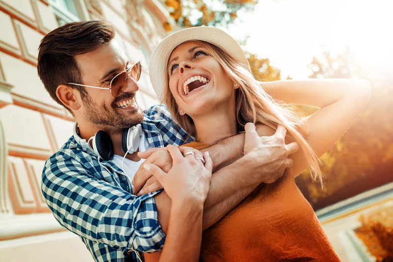 man hugging smiling woman from back outside