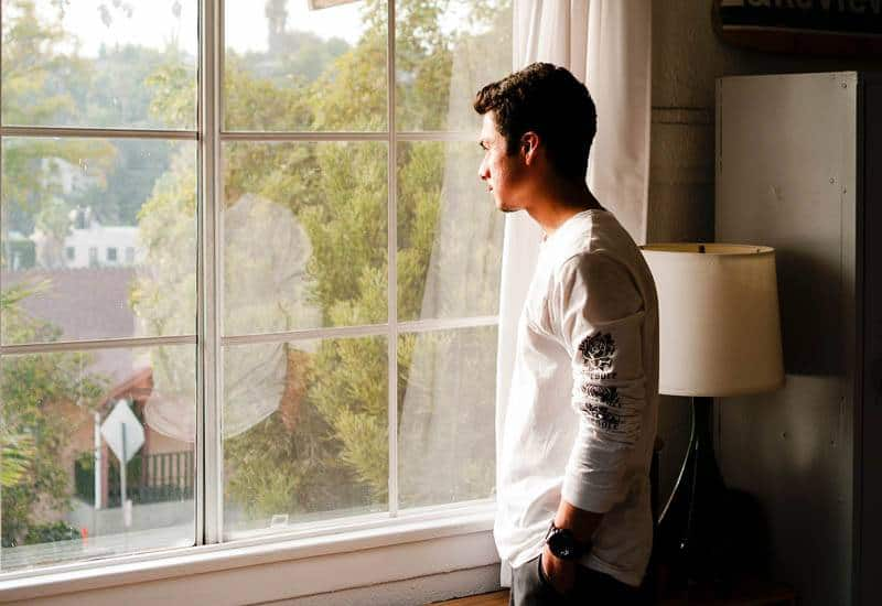 man in white t-shirt stands beside window and looking out