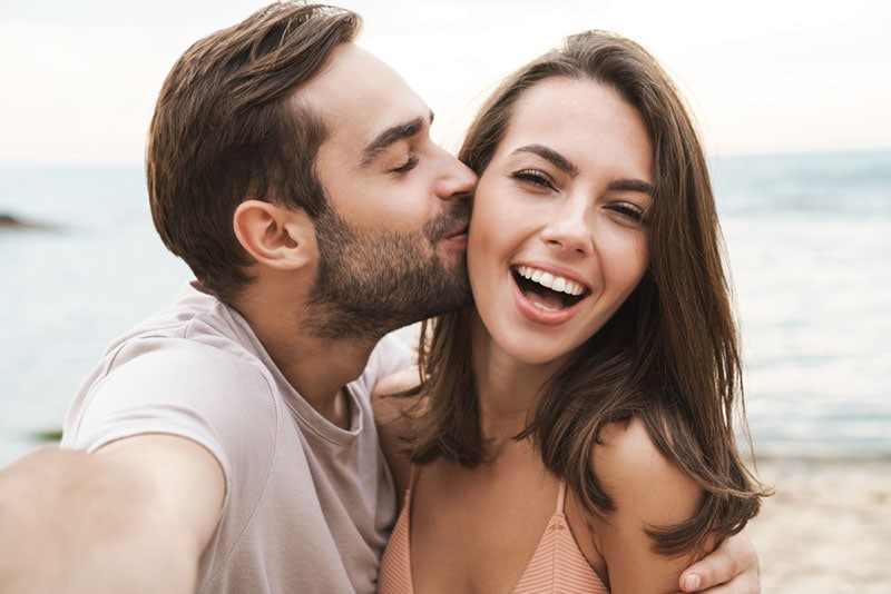 man kissing smiling woman on the beach