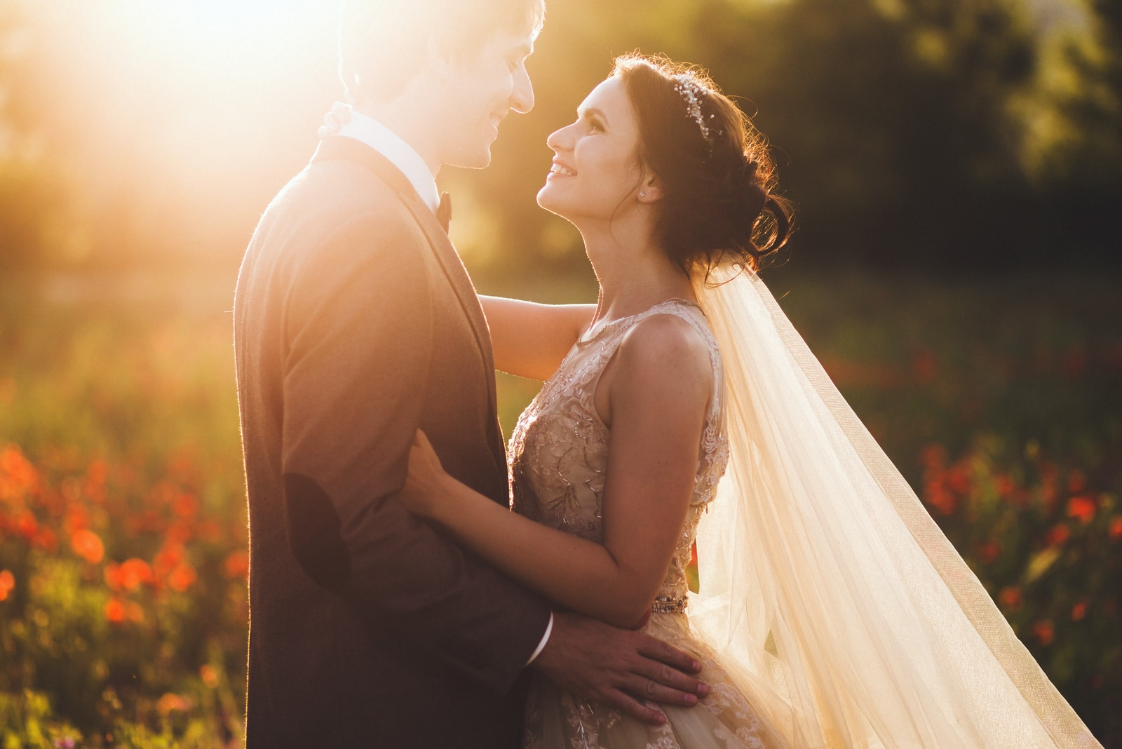 newlyweds in nature hug at sunset