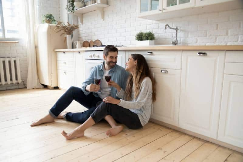 romantic couple sitting on kitchen floor and drink wine while looking at each other smiling