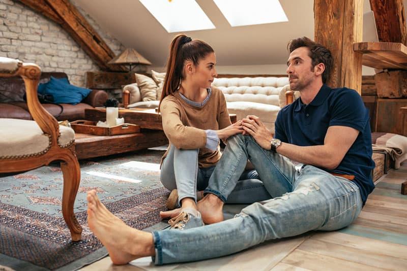 serious couple talking on the floor
