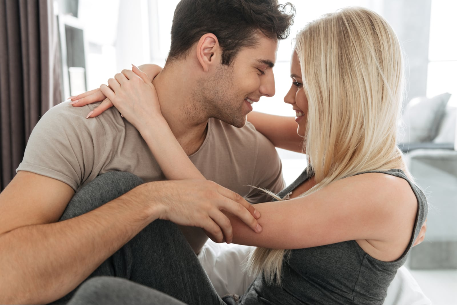 the attractive couple hugs passionately and looks at each other in the house