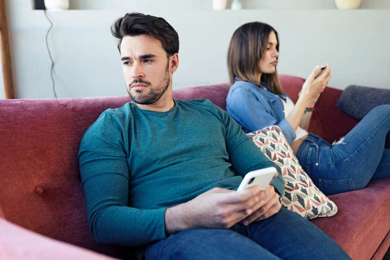 upset man holding phone and sitting next to woman