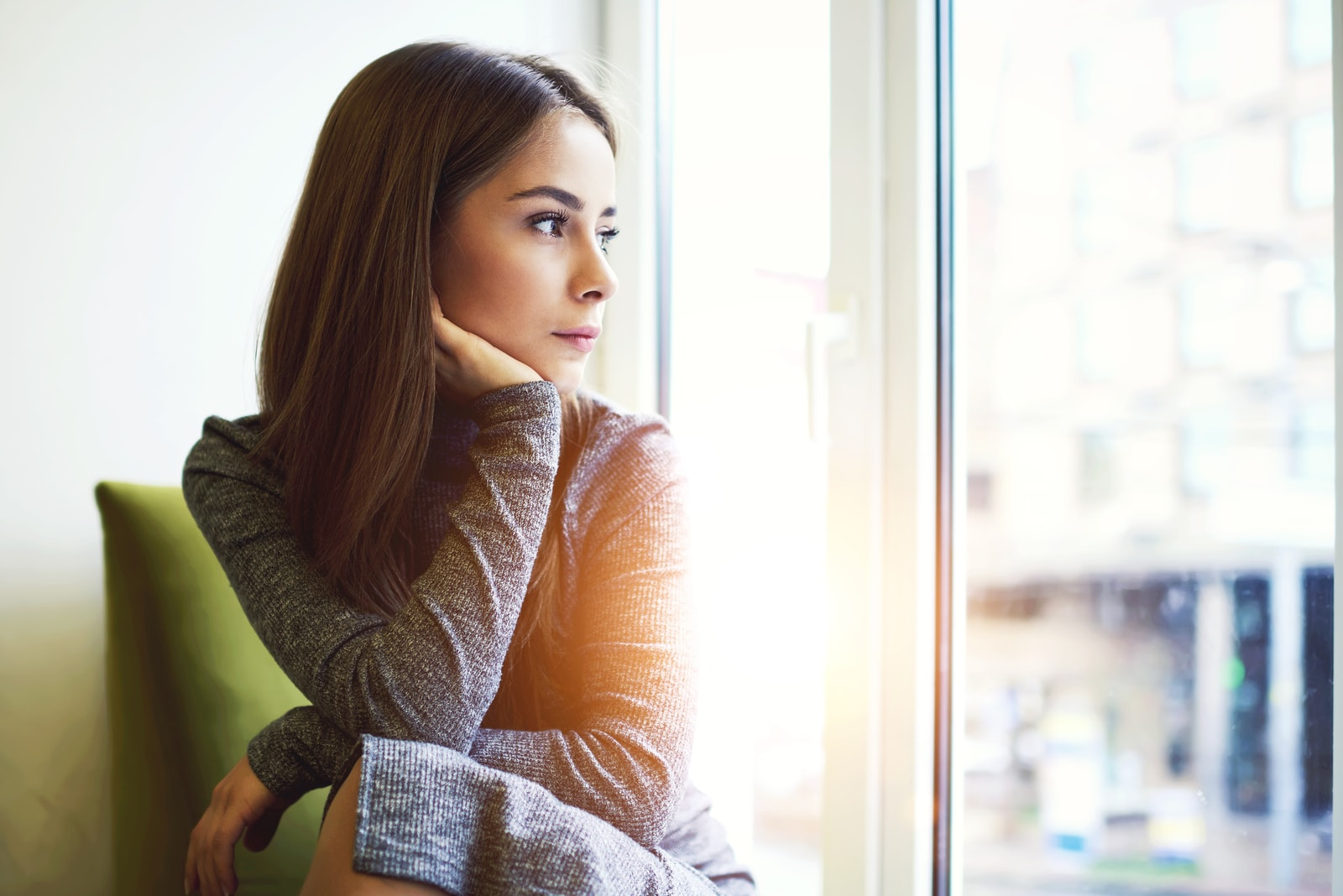 young mindful woman looking through the window