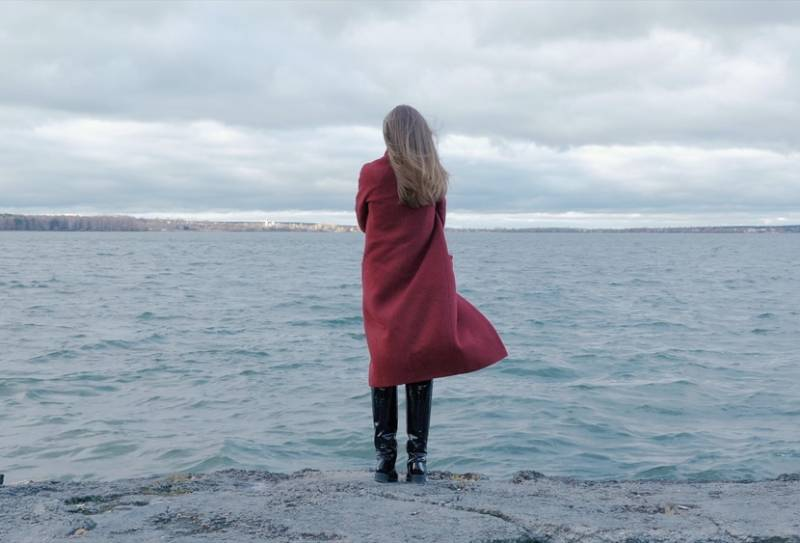 woman in red coat standing on the beach