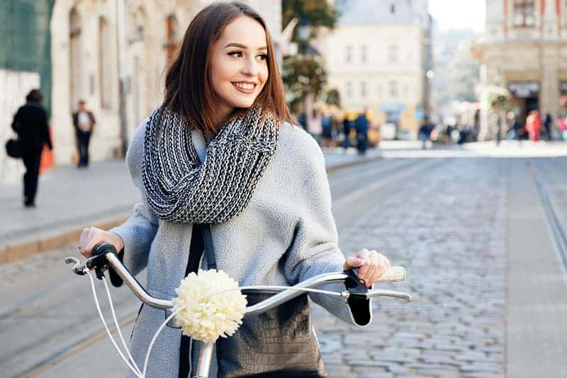 Lovely young woman posing with bike on the street