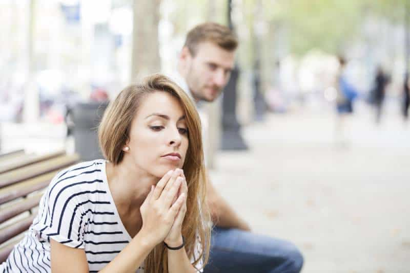 Portrait of young woman and young man outdoor on the street having relationship problems