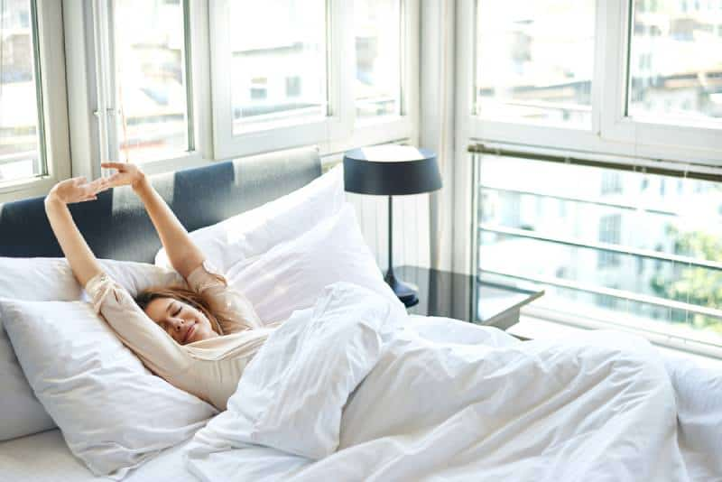 Woman stretching in bed with arms raised
