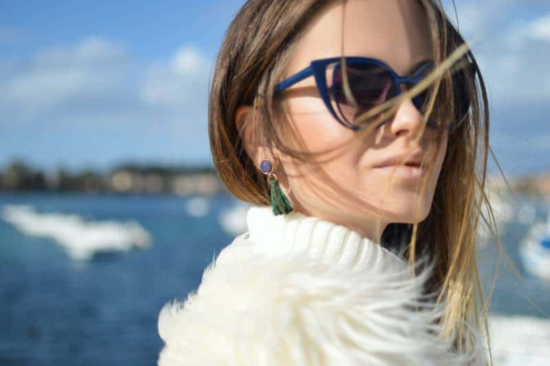 Woman wearing blue framed cat eye sunglasses with water in background