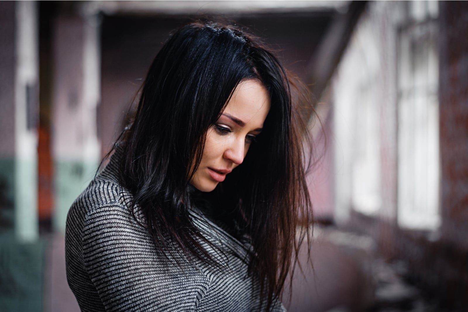 a woman with black hair with a downcast look