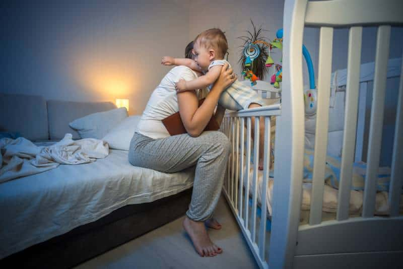baby hugging young caring mother