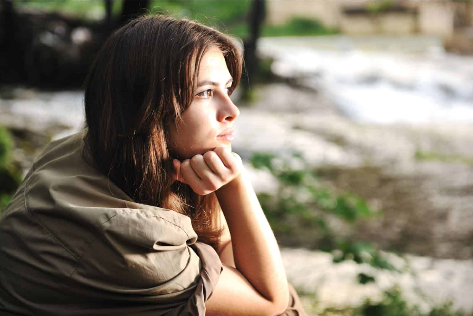 lonely pensive woman sitting alone in nature