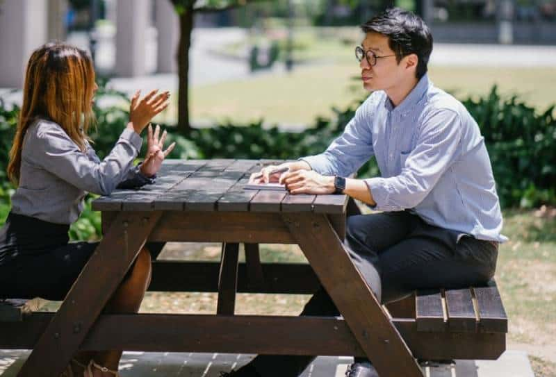 male and female talking outside on table
