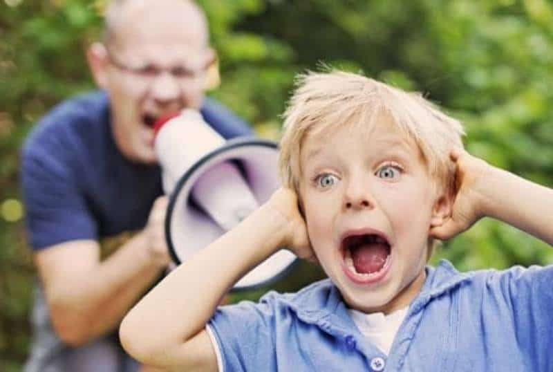 man yelling on megaphone at kid