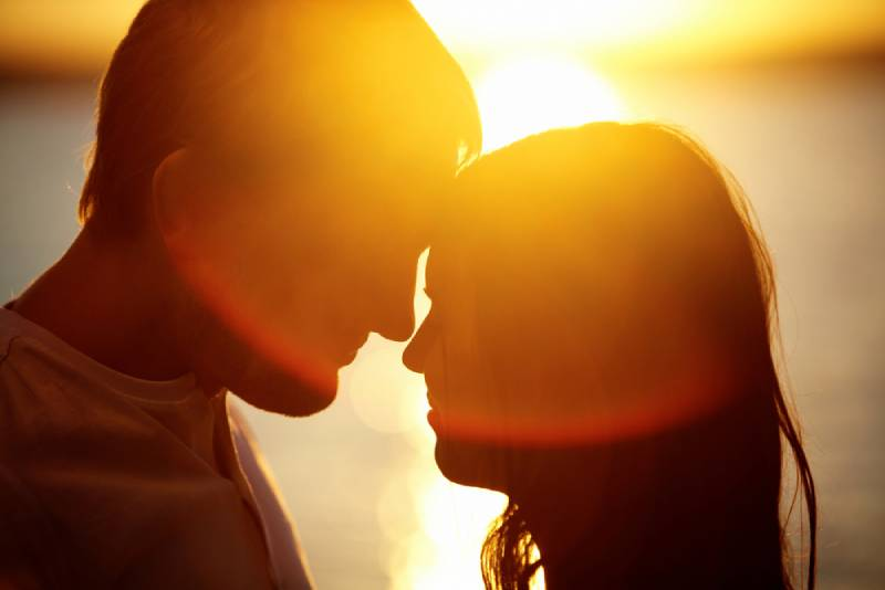 romantic couple looking each other on background of sunset