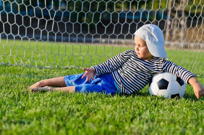 small boy in a cap lying on the grass