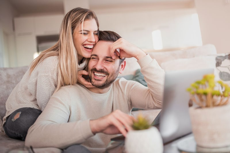smiling woman hugging man in the living room