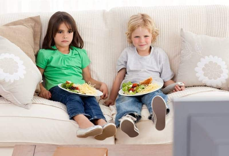 two children sitting on couch and watching a tv