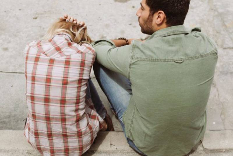 woman covering her head with hands while her man stands next to her