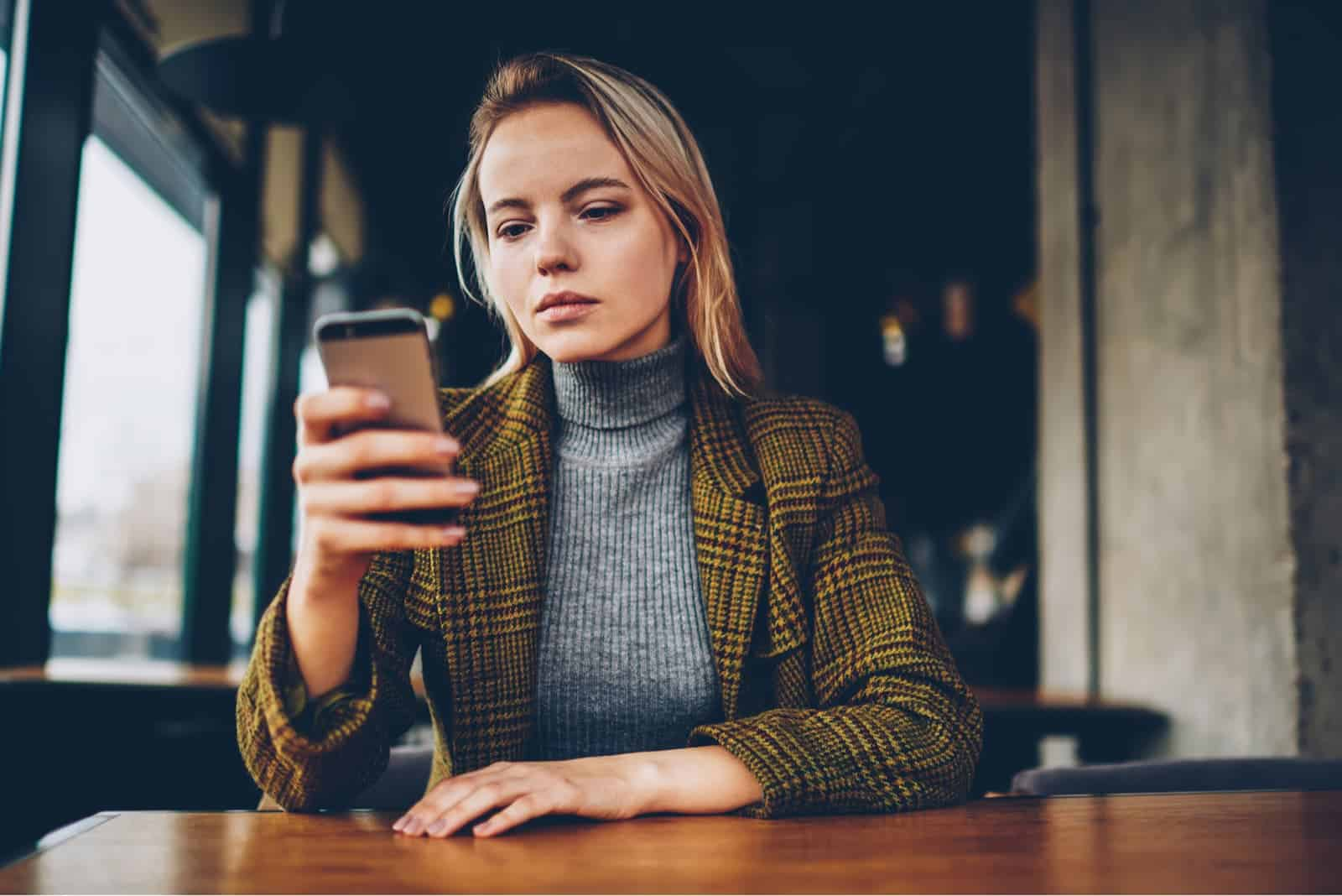 woman sitting by the table holding her phone