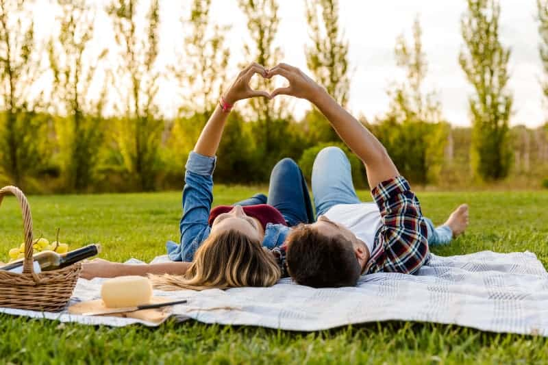 Couple make heart while lying on grass