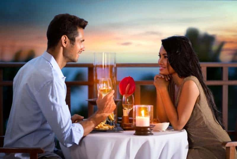 Happy couple on summer evening having romantic dinner