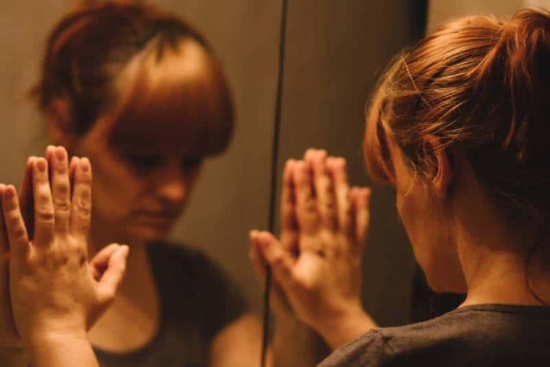 Sad and lonely woman looking at her reflection in the mirror