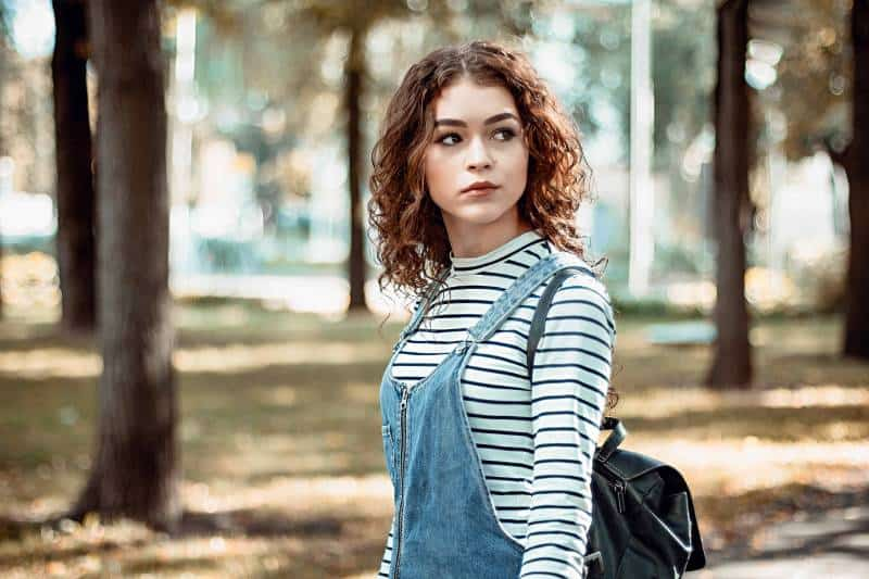 Woman with curly hair standing in the park