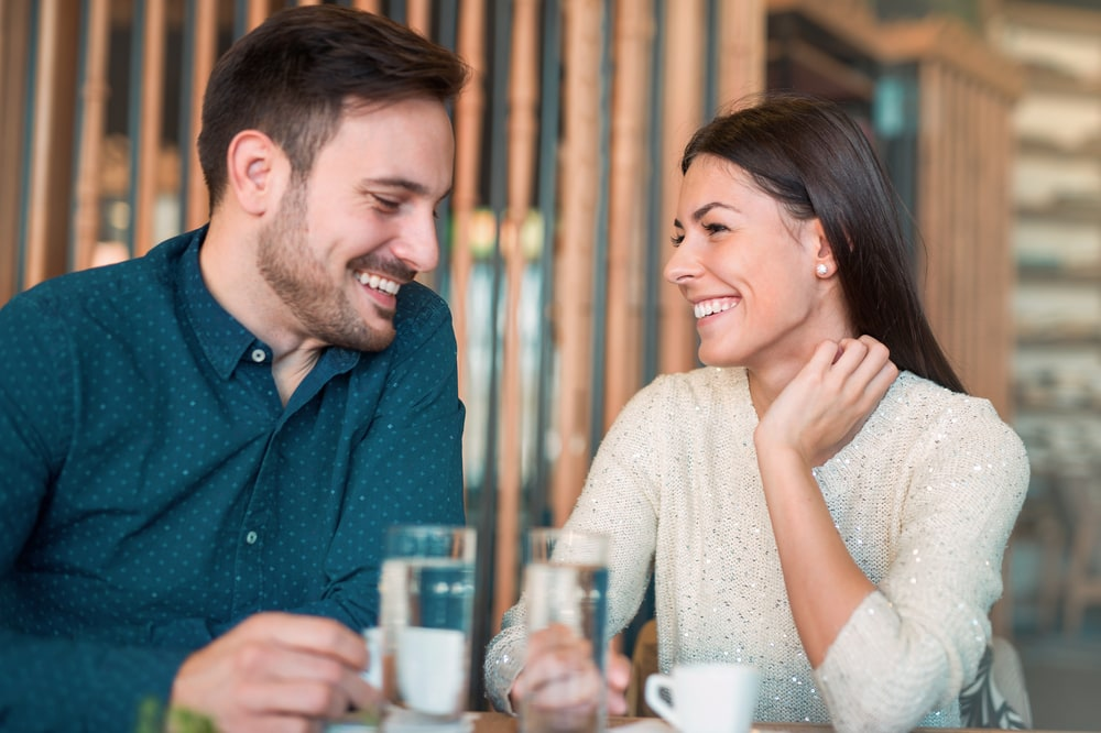 a handsome man and a brunette are flirting in a cafe