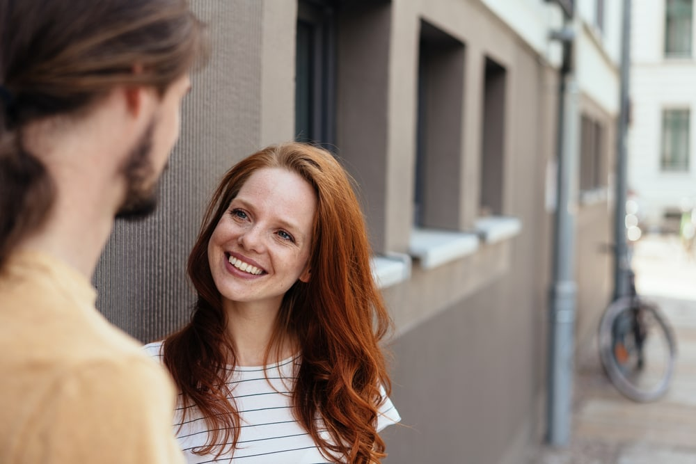 a red-haired smiling girl on the street talking to a man
