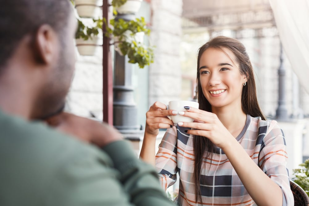 a smiling woman sits in a cafe with a black man and drinks coffee