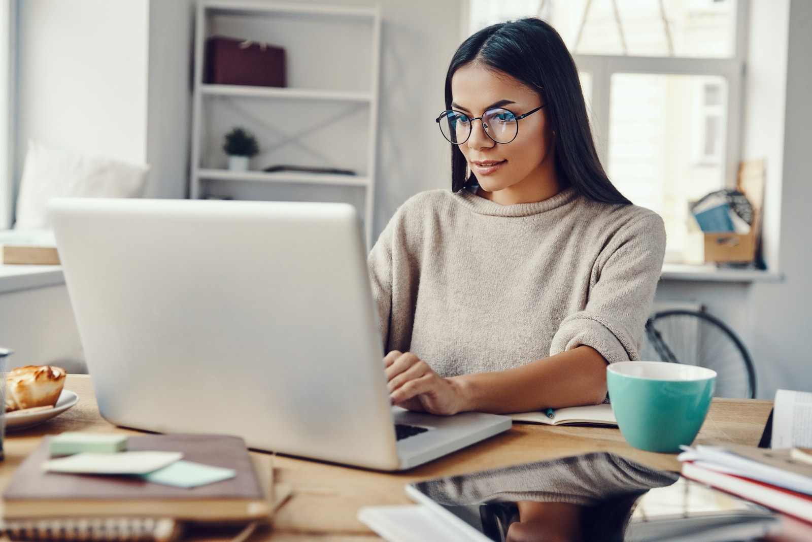 a woman sits at a laptop and works