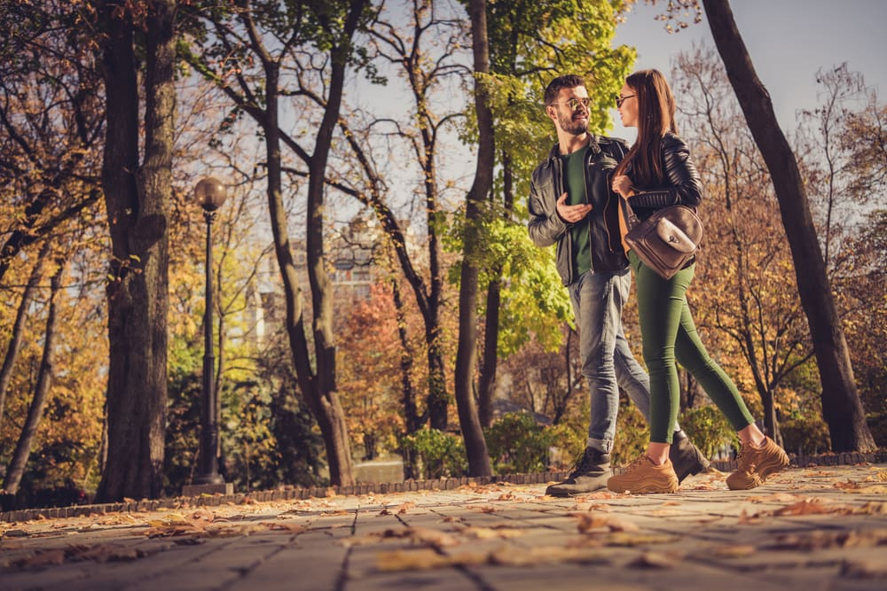 an attractive couple walks in the park and talks