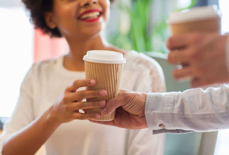 close up of smiling african woman hand taking coffee cup from man