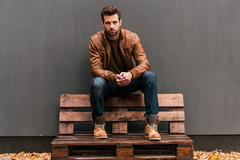 confident man sitting on the wooden bench