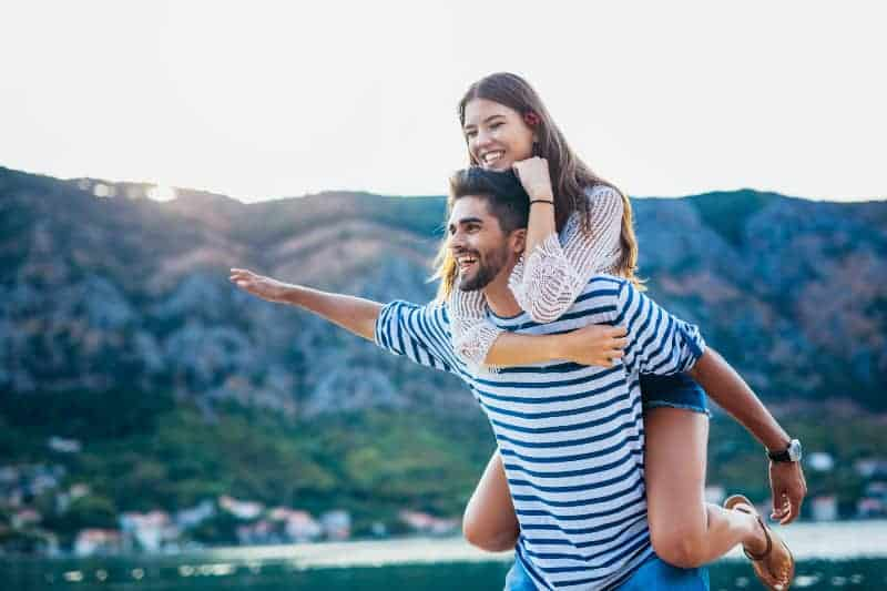 happy man piggybacking woman during daytime