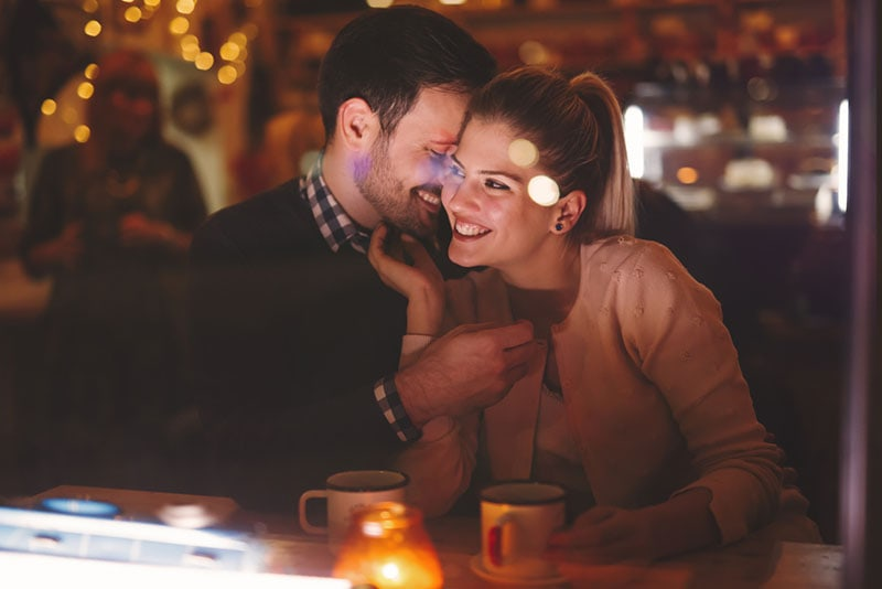 man cuddling with woman at cafe