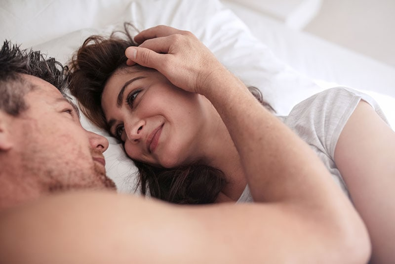 man cuddling with woman in bed