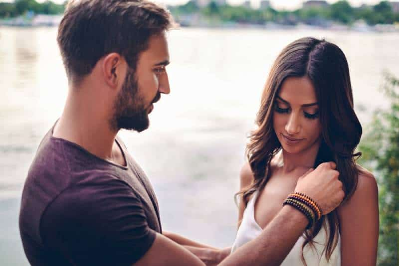 man touching woman's hair by the water