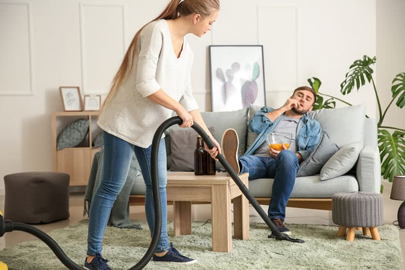 woman cleaning floor while her boyfriend watching tv
