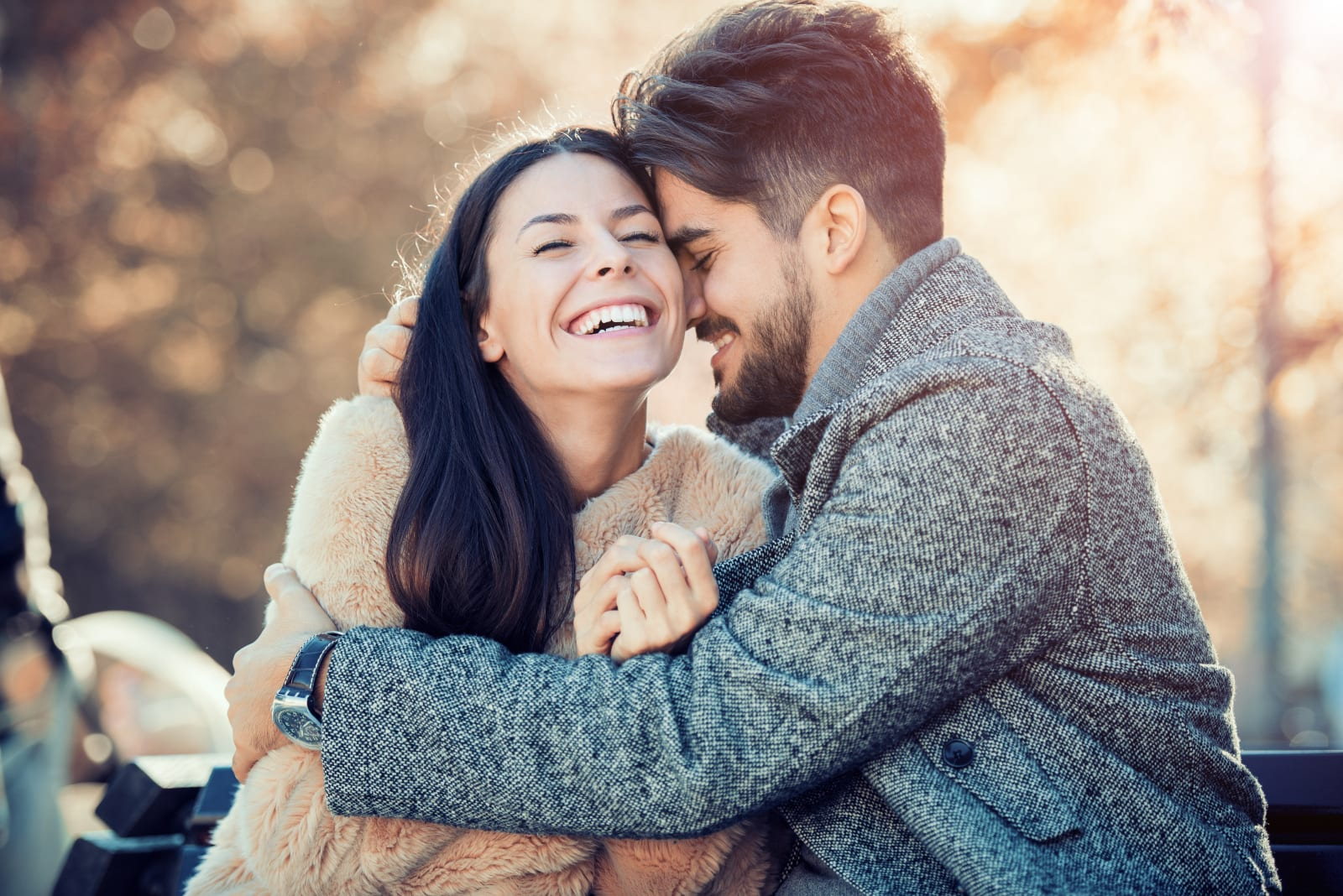a happy man hugging a smiling woman tightly