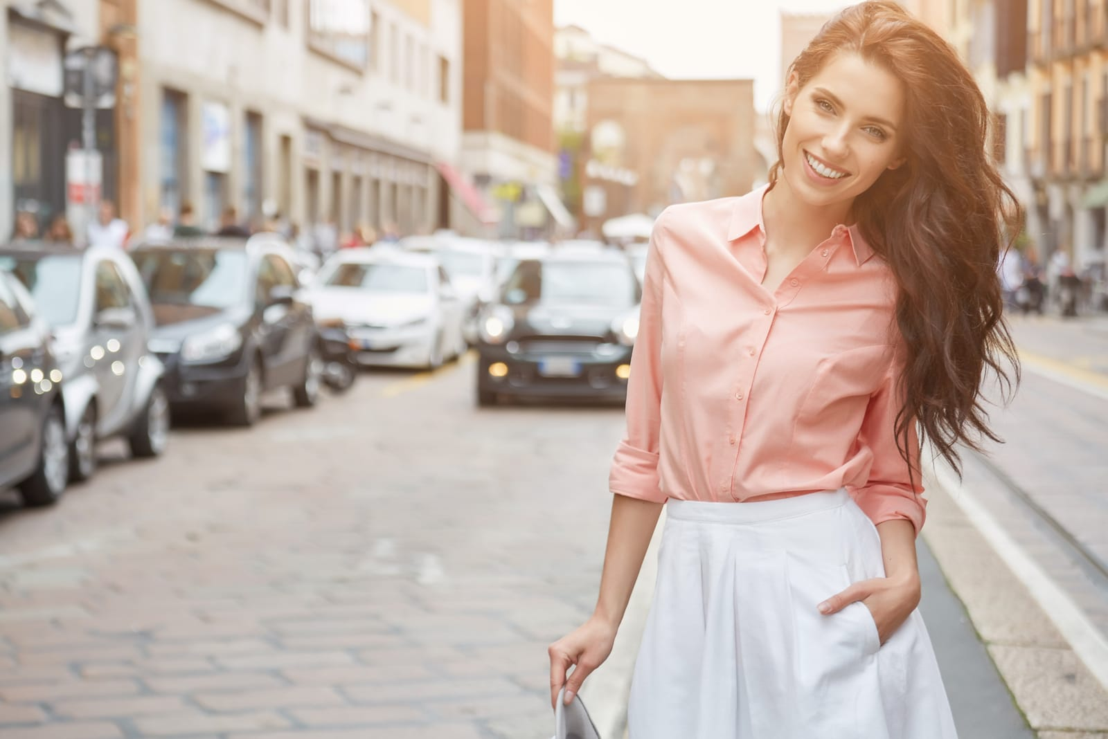 a woman with long brown hair stands in the street and laughs