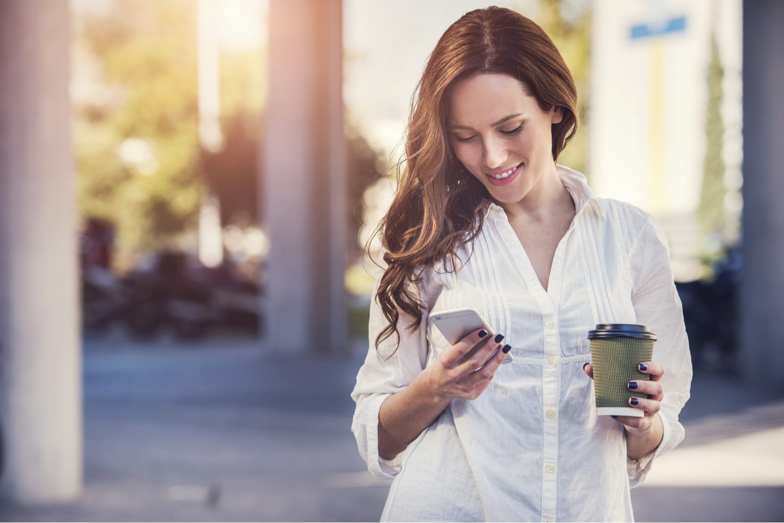 beautiful smiling brunette uses a smartphone