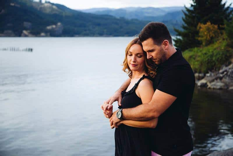 man hugging woman from back by the lake