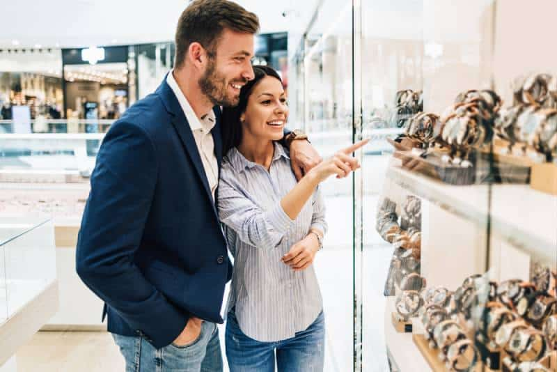 smiling couple in front of jewerly store
