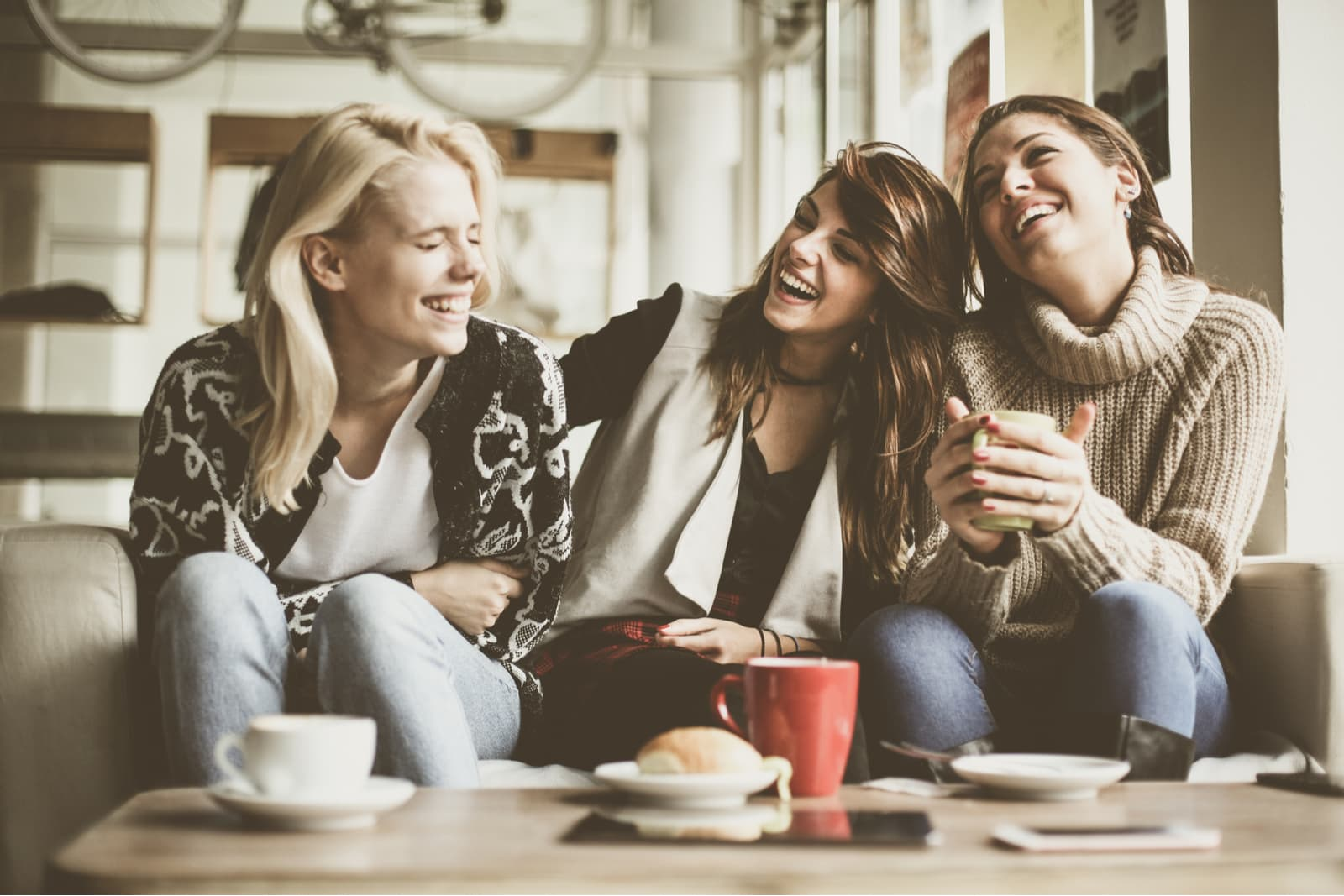 smiling friends sit, drink coffee and talk