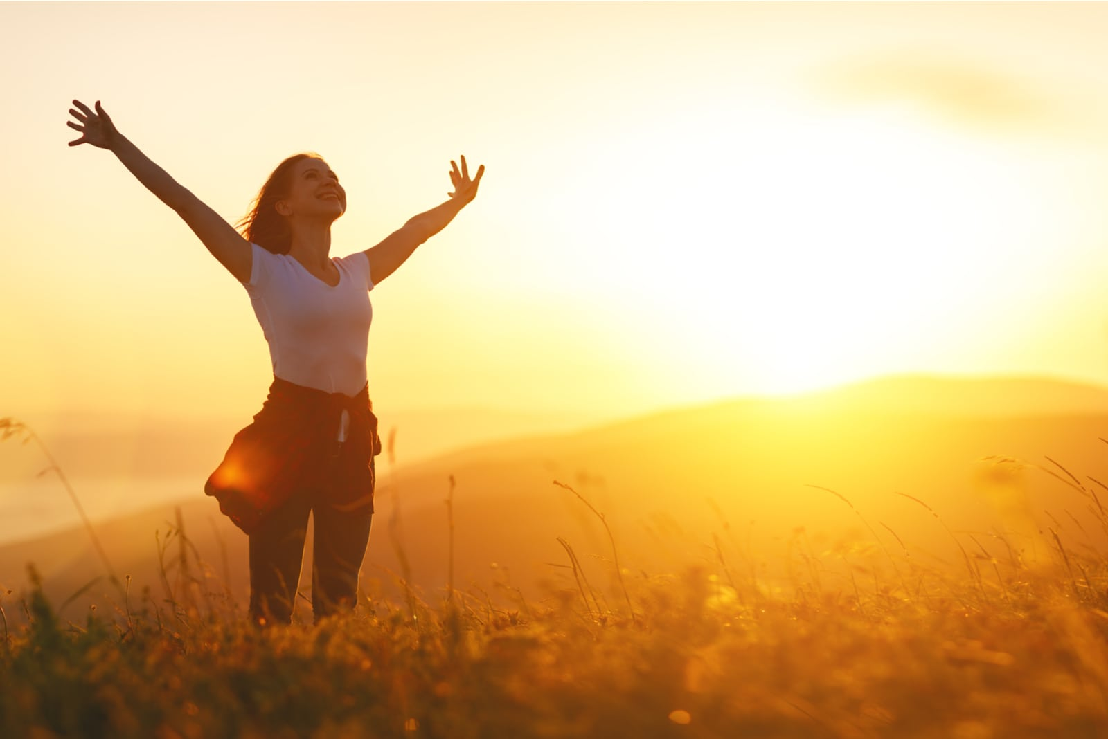 the woman stands in a field of outstretched arms