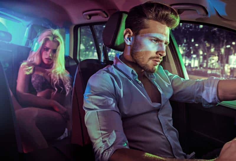woman in underwear sitting in backseat of car while man driving