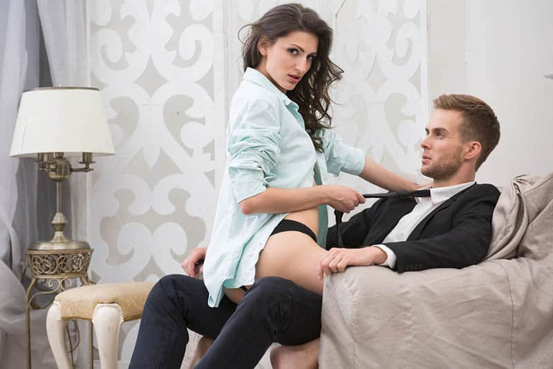 woman in underwear sitting on man with suit on sofa